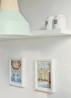 Framed photos of house interiors, tea caddies and metal lamp with wooden bulb socket by young designer