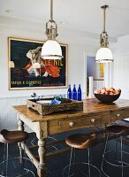 Rustic table and stools under vintage, industrial pendant lamps