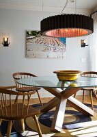 Ring-shaped pendant lamp above round table with solid wooden base and wooden armchairs on sisal rug