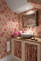 Illuminated washbasin on base unit with red and white patterned fabric panels in doors and matching wallpaper in attic room