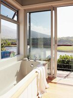 Bathtub with magnificent view of South African lagoon landscape through open terrace doors