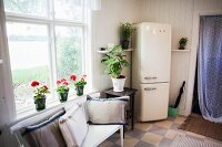 Simple bench with scatter cushions below window, red geraniums on windowsill and retro fridge-freezer