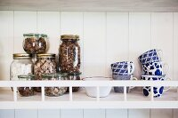 Storage jars and white and blue painted mugs on wall-mounted shelf