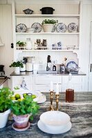 Potted herbs on counter opposite decorative, blue and white painted plates on dresser in rustic interior