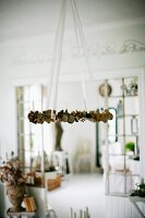 Wreath suspended from ceiling on white ribbons in rustic interior