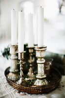 White candles in silver candlesticks on vintage tray