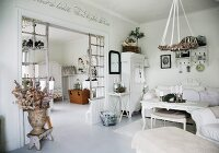 Rustic, white interior with wreath suspended above coffee table, lattice partition and view into dining room