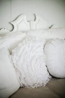 Scatter cushions with white covers, some pleated or ruffled