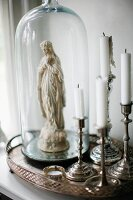 Silver candlesticks next to Madonna figurine under glass covers on silver tray