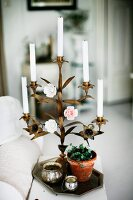 White candles in brass, floral candlestick with coloured rose ornaments on tray amongst potted plant and silver pots