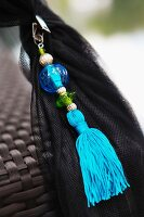 Oriental, light blue tassel threaded with beads on black mosquito net