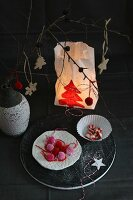 Festive table arrangement and candle lantern made from painted paper bag