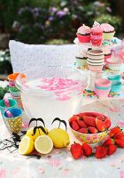 Colourful, edible decorations for garden party on table with floral tablecloth