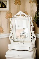 Dressing mirror with carved frame painted white on small table in corner