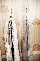 Scarves hanging from vintage coat hooks on wallpapered wall