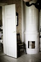 Round, white-tiled stove in corner of traditional room