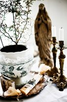 House plant in painted china pot and antique candlesticks in front of Madonna figurine