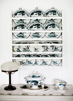 Painted decorative plates on wall rack above antique table lamp and china crockery on surface