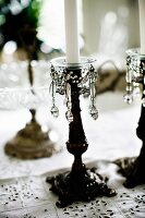White candles in antique candlesticks with beaded ornaments on tablecloth