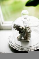Cherub figurine under glass cover on windowsill
