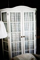 White-painted, glass-fronted cabinet with patterned curtains behind doors