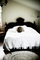 French bed with black, carved headboard and white bedspread in master bedroom in attic