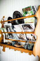Magazines in carved wooden rack on white wooden wall