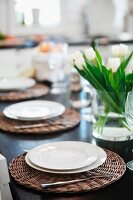 Table festively set with white plates on wicker place mats and glass vase of tulips