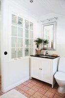 White washstand with black counter below silver mirror; shower area screened by wall with lattice window to one side