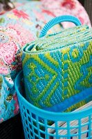 Patterned beach mat in pale blue plastic basket