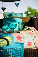 Table decorated with coloured glasses on patterned tablecloth outdoors