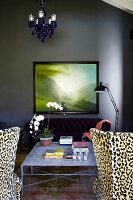 Leopard-patterned armchairs next to delicate, metal coffee table and framed landscape painting on dark grey wall