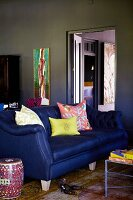 Colourful scatter cushions on dark blue sofa in room with walls painted dark grey