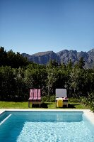 Pool and sun loungers in garden against backdrop of mountain landscape