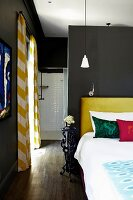 Bed with scatter cushions against headboard upholstered in yellow against grey wall