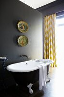 Free-standing, vintage bathtub against grey partition in front of window with yellow and white patterned curtain