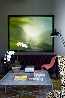 Orchid on delicate, metal coffee table in front of framed landscape painting on dark grey wall