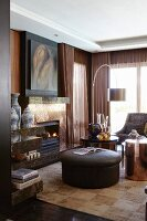 Classic elegant room in shades of brown with fireplace, designer standard lamp and leather ottoman