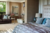 Elegant lounge area with beige textile wallpaper and bedroom area with button-tufted headboard