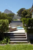 Elegant pool area in garden with steps, view of mountains and blue sky