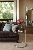 Eileen Gray side table, brown velvet sofa and beige carpet in elegant living area