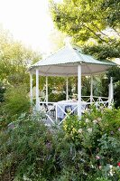 Gazebo with corrugated metal tent roof surrounded by blooming flowerbeds