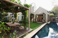 Narrow, courtyard pool and climber-covered pergola over terrace with table and chairs on wooden deck