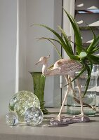 Ornamental glass spheres and long-legged bird ornament in front of aloe leaves in vase