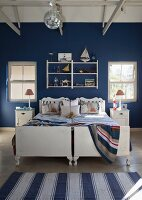 Twin beds against wall painted dark blue in bedroom with maritime ambiance