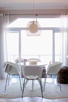 Dining set with white shell chairs at round table on animal-skin rug in front of open balcony door