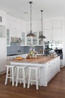 Free-standing island counter with white bar stools below pendant lamps with metal lampshades in open-plan country-house kitchen
