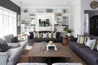 Sofa set around wooden coffee table in front of white, fitted shelving