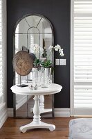 Orchids on white, round side table in front of arched, full-length mirror leaning against dark wall