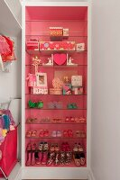 Girl's shoes and decorative storage boxes on glass shelves in open-fronted unit with pink internal walls